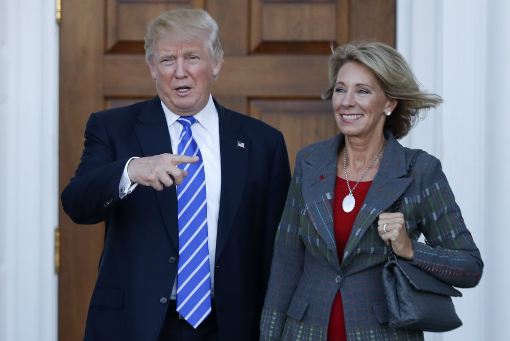President-elect Donald Trump and Betsy DeVos pose for photographs Saturday at the Trump National Golf Club Bedminster clubhouse in Bedminster, N.J. Trump has chosen DeVos, a charter school advocate, to be education secretary in his administration.
