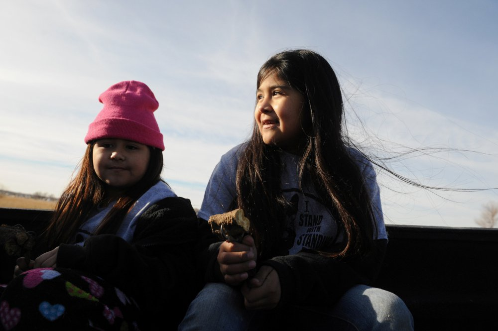 Girls from the Pomo tribe ride in the back of a truck during a protest Friday against Dakota Access pipeline plans.
