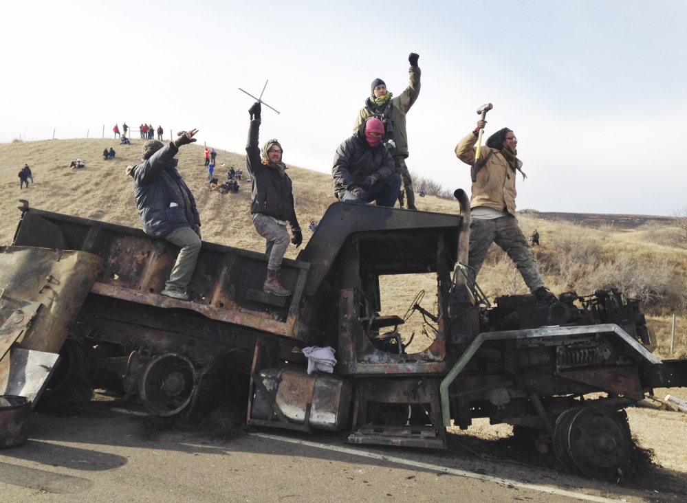 Protesters against the Dakota Access oil pipeline stand on a burned-out truck near Cannon Ball, N.D., on Nov. 21. Hundreds have been arrested at the protest site.