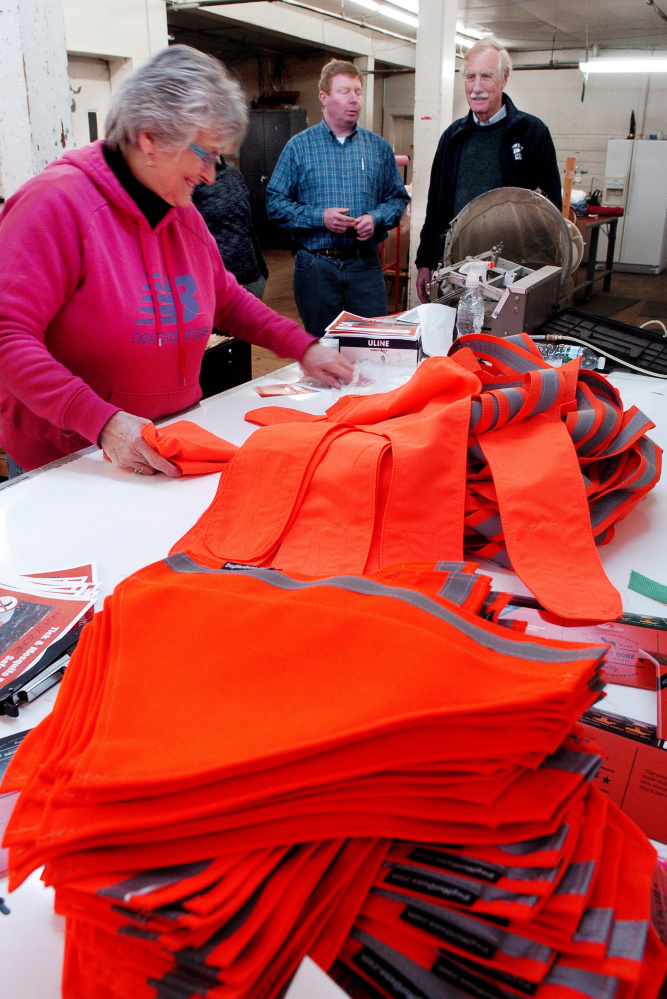 U.S. Sen. Angus King, I-Maine, right, watches as Maine Stitching Specialties employee Alice Quirion works on a safety dog vest Tuesday at the Skowhegan company as owner Bill Swain speaks about the company products.