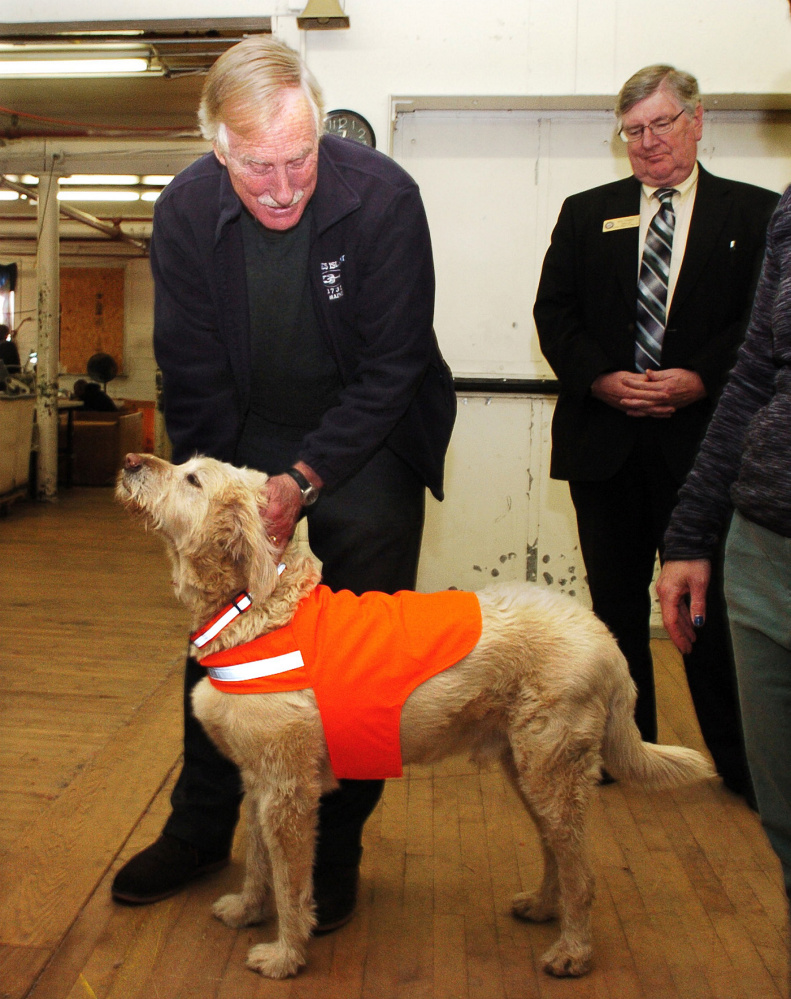 U.S. Sen. Angus King, I-Maine, pets Maine Stitching Specialties mascot dog Max, wearing a company safety dog vest, during a tour of the Skowhegan company on Tuesday. Ben Tucker is at right.