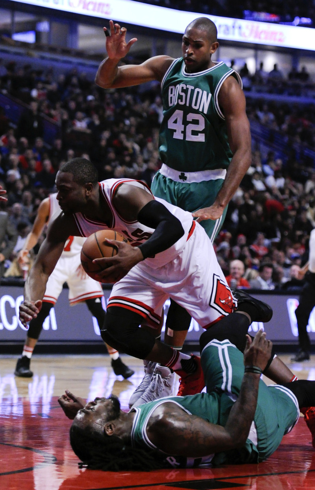 Chicago Bulls' Dwyane Wade, center, is called for an offensive foul against Celtics forward Jae Crowder (99) as Celtics center Al Horford (42) looks on during the second quarter of a game last Thursday in Chicago.