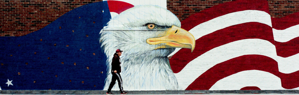 Skowhegan Village plaza owner Dana Cassidy inspects a large mural showing an American flag and an eagle being painted Thursday outside the Maine Veterans Museum, which is under construction in Skowhegan.