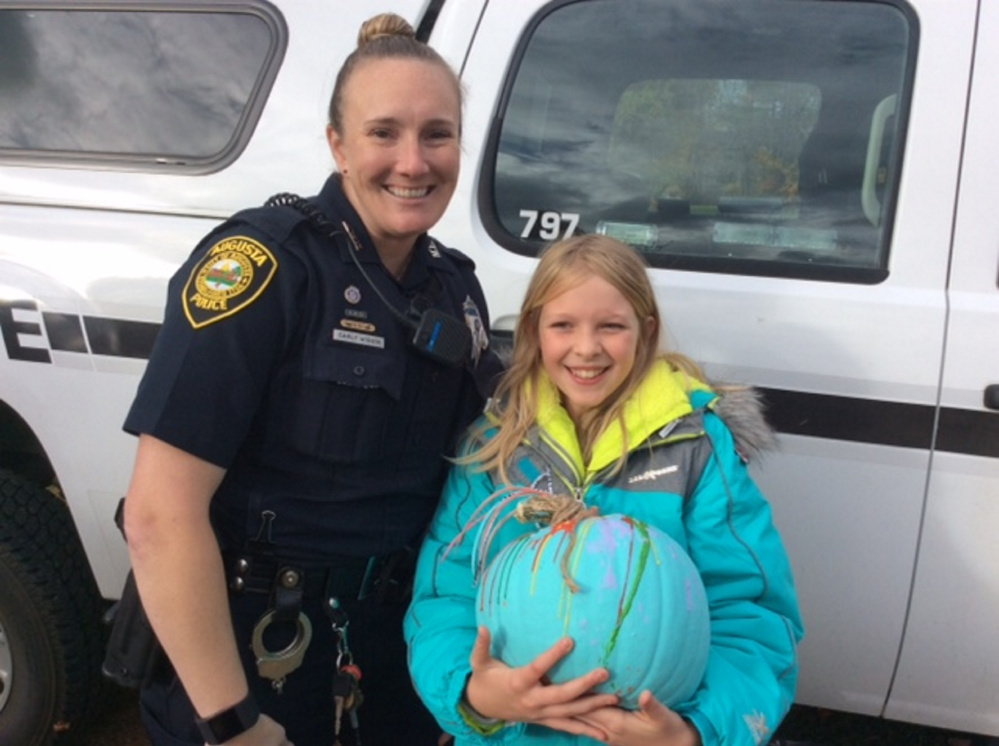 Ryleigh Miranda with pumpkin #6 with Officer Carly Wiggin.