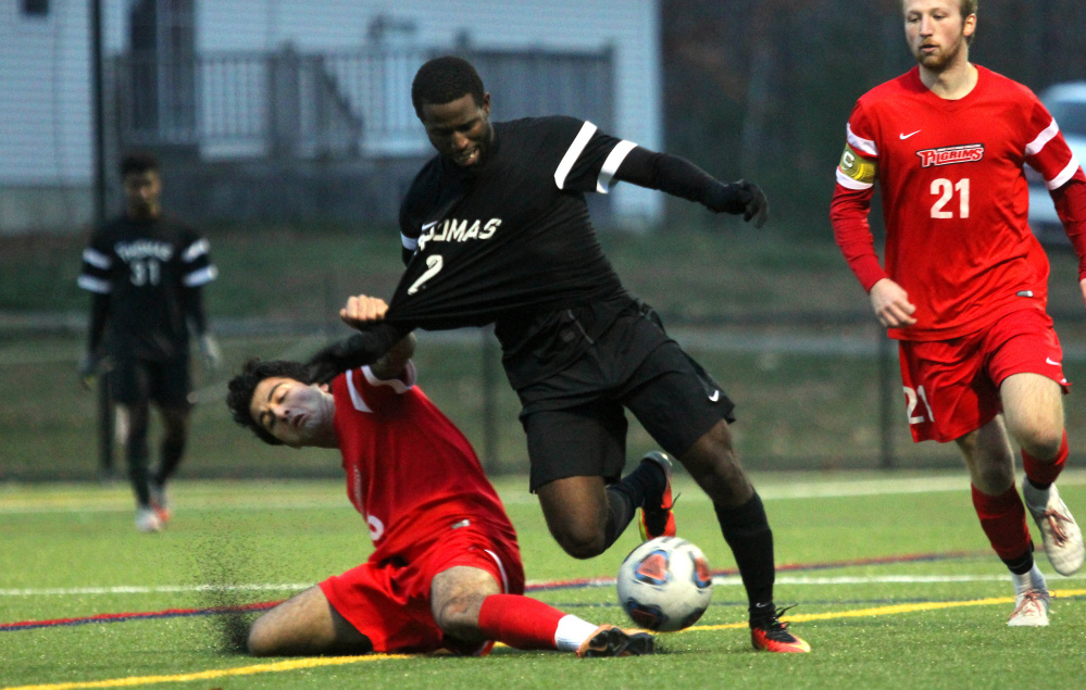 Thomas College's Tevin Reid gets dragged down by New England College's Sina Simali in the second half of the North Atlantic Conference championship in Waterville on Saturday night.