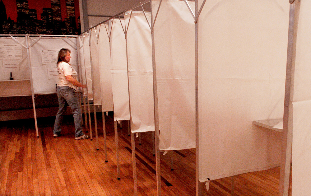 Dacia Rancourt fills the dozens of voting booths with instructions at the American Legion hall in Waterville on Monday, in preparation for Election Day.