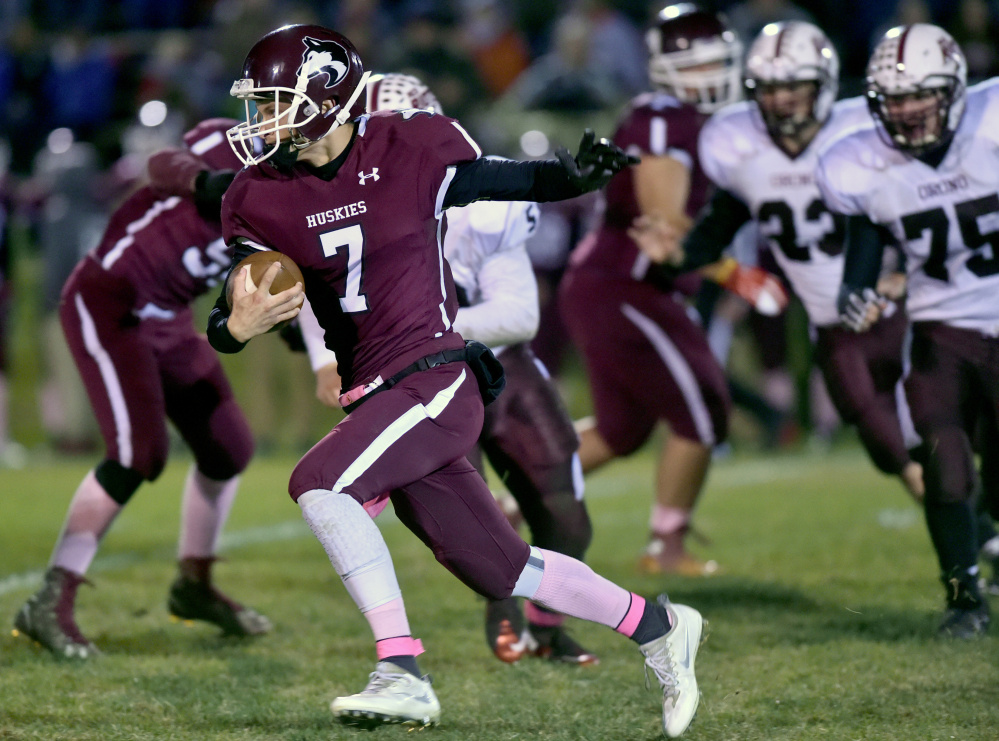 Maine Central Institute quarterback Josh Buker runs for extra yards during a Little Ten Conference game against Orono earlier this season.