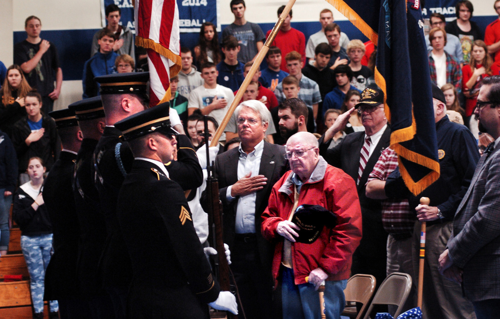 World War II veterans George Prentiss, of Fairfield, front, and Steve Ball join Erskine Academy students and staff members Tuesday in a color guard posting of flags during a salute to veterans for the upcoming Veterans Day holiday at the South China school.