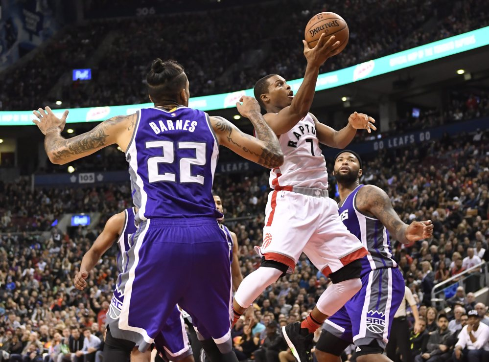 Toronto Raptors guard Kyle Lowry (7) goes for a layup past Sacramento  forward Matt Barnes (22) and center DeMarcus Cousins during second half of a game Sunday.