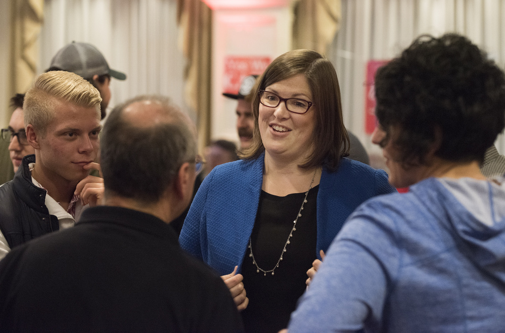 Emily Cain greets and hugs supporters early Wednesday morning at the Hilton Garden Inn ballroom in Bangor.