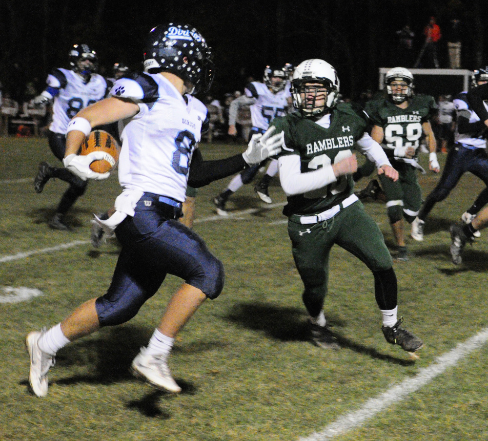 Staff photo by Joe Phelan   Dirigo's Cameron Turner, left, gets chased toward the sidelines by Winthrop's Antonio Meucci during a Class D South semifinal Friday at Maxwell Field in Winthrop.