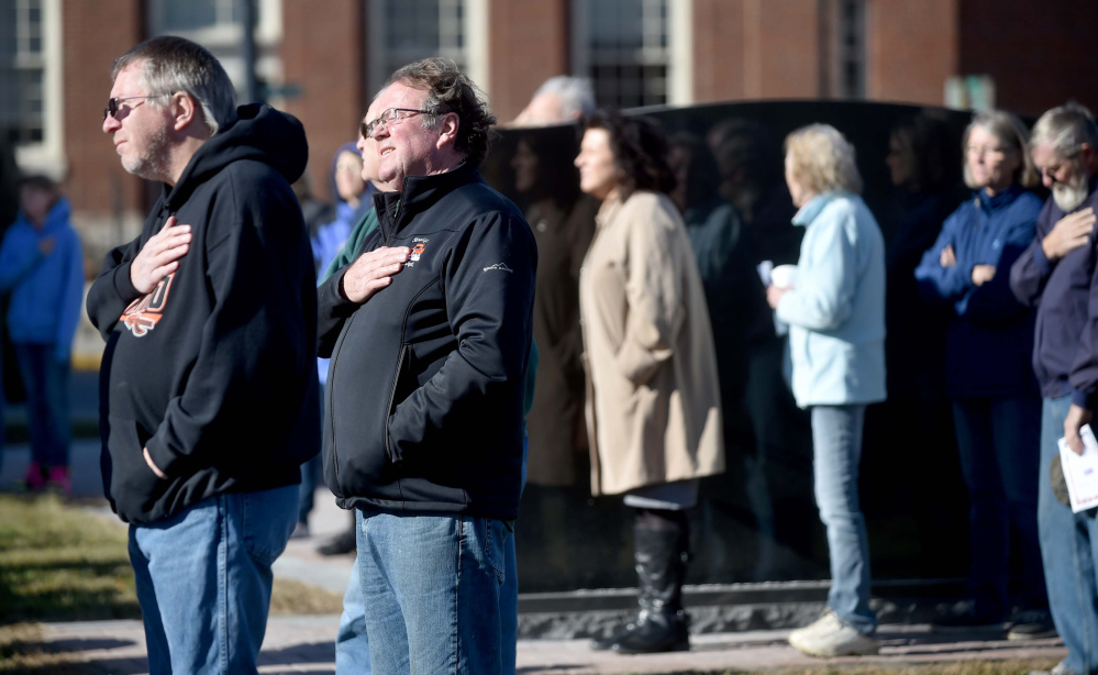 People listen to the National Anthem on Friday during a re-dedication of the Veterans Memorial Park in Skowhegan.
