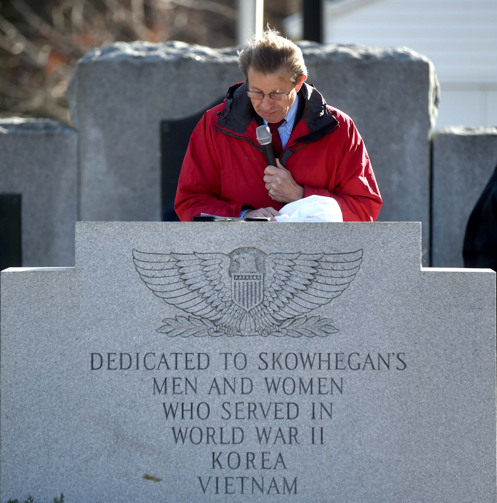 Peter Mills, president of the Maine Turnpike Authority, speaks at a lectern Friday during a re-dedication of Veterans Memorial Park in Skowhegan.