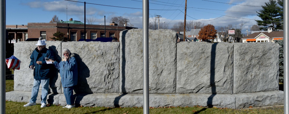 A couple finds relief from the wind Friday behind the veterans' memorial wall during a re-dedication of Veterans Memorial Park in Skowhegan.