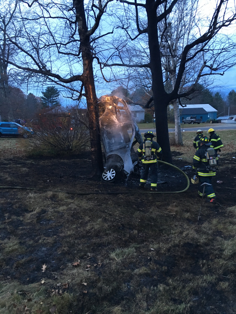 West Gardiner firefighters douse the remaining flames in an overturned burning sport-utility vehicle Sunday near the intersection of High Street and Hallowell-Litchfield Road in West Gardiner. The vehicle caught fire after striking a tree about 6 a.m. while its driver was on his way to work.