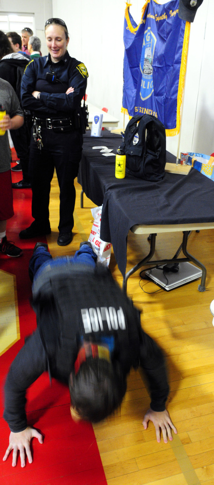 Augusta police school resource officer Carly Wiggin watches as a student tries to see how many push-ups he can do while wearing a tactical vest during a college and career fair Thursday at Cony High School. Students were trying to do the same thing at the U.S. Marine Corps booth.