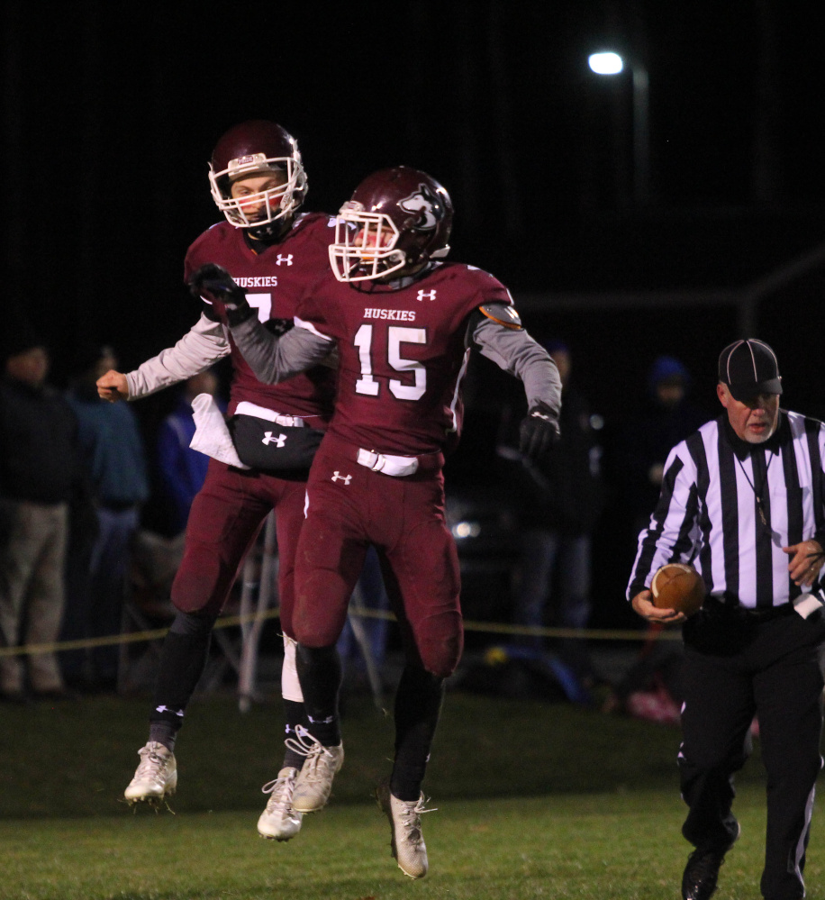Maine Central Institute quarterback Josh Buker, upper left, celebrates a first-half touchdown run with Clark Morrison (15) during a Little Ten Conference semifinal game earlier this month in Pittsfield.