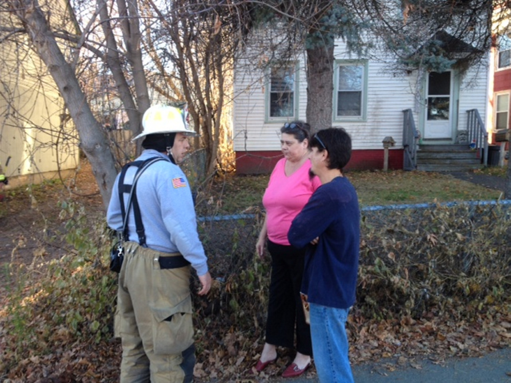 Waterville fire Captain John Gromek (left) tells Cheryl Jack that her cat is OK and escaped a fire Saturday afternoon at the apartment building she lives in on Front Street in Waterville. At right is her next door neighbor, Jeffrey Mello.