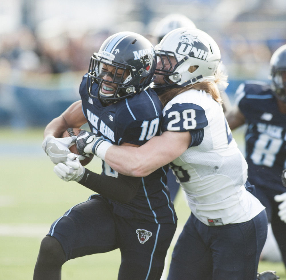 UMaine's Micah Wright can't escape the grasp of UNH defender Zaire Williams during the first half of a pivotal regular season finale for both teams Saturday in Orono. The Wildcats won 24-21 to end Maine's season.