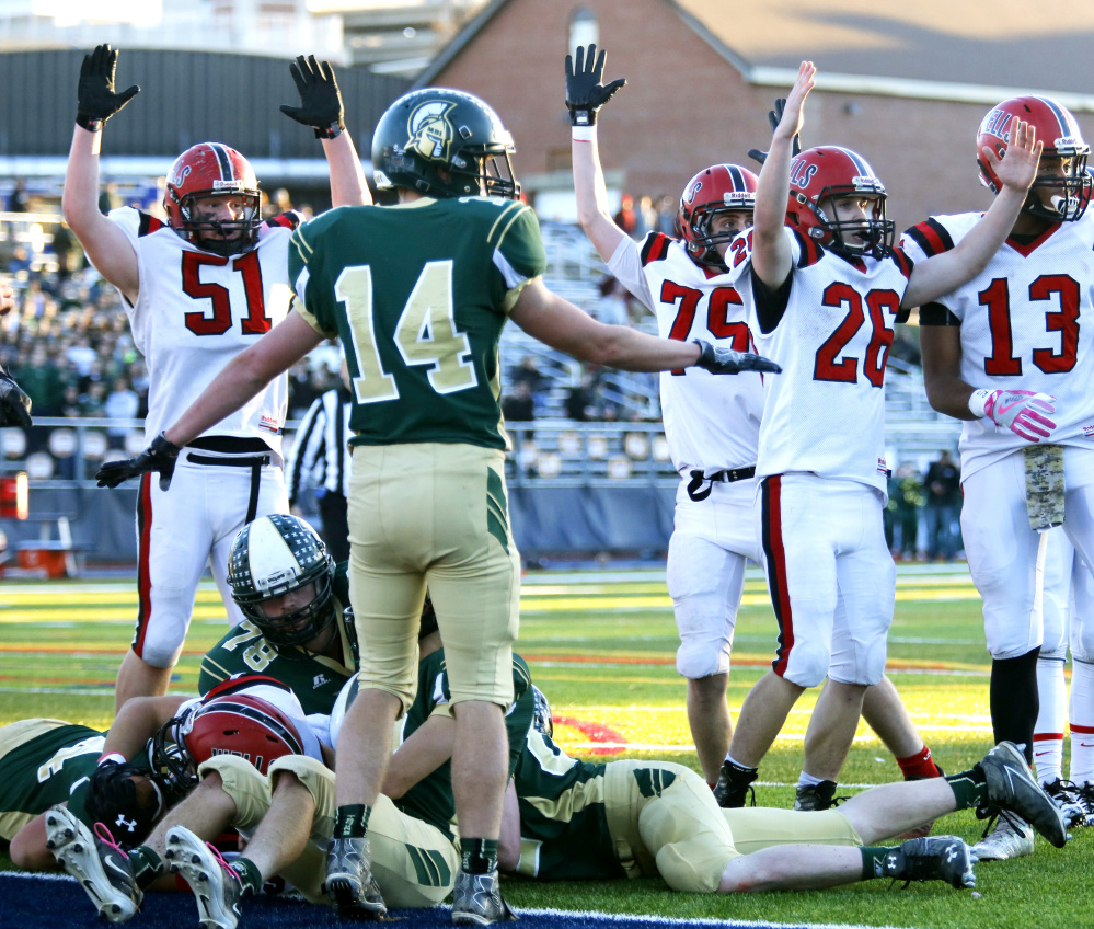 A host of Wells players signal for a touchdown during the Class C state championship game Saturday against Mount Desert Island at Fitzpatrick Stadium.