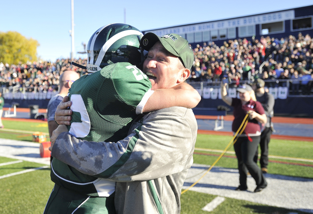 Bonny Eagle coach Kevin Cooper hugs Keith Hoffses after the Scots beat Portland for the Class A state championship Saturday afternoon at Fitzpatrick Stadium in Portland.