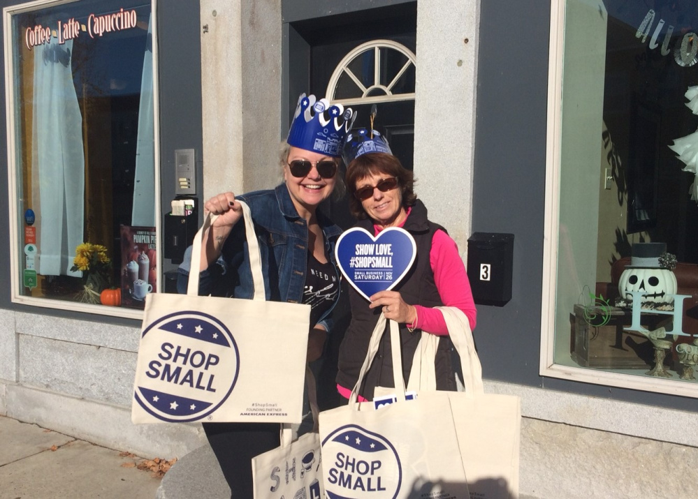 Winthrop Lakes Region Chamber Vice President and owner of Bloom Salon Kim Stoneton, left, and Chamber Executive Director Barbara Walsh hand out Shop Local bags and other items to promote Small Business Saturday and the Winthrop Region's Progressive Shopping Day on Nov. 26.