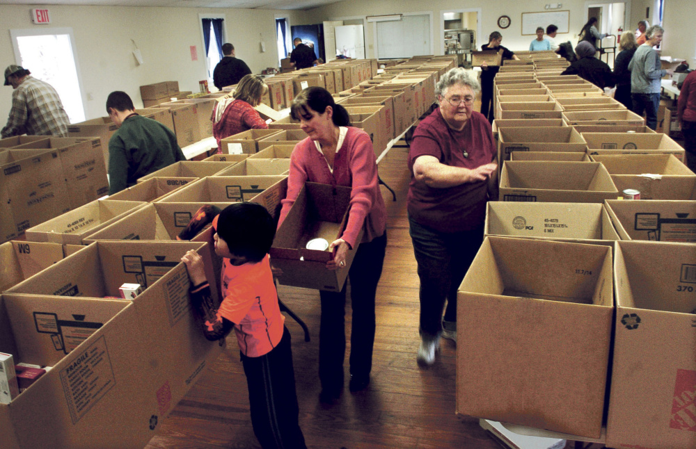 Volunteers fill nearly 200 Thanksgiving food boxes at the Federated Church in Skowhegan on Monday. Betsy Drumm, right, president of the church women's fellowship, fills boxes as Heather Johnson and her son John work together.