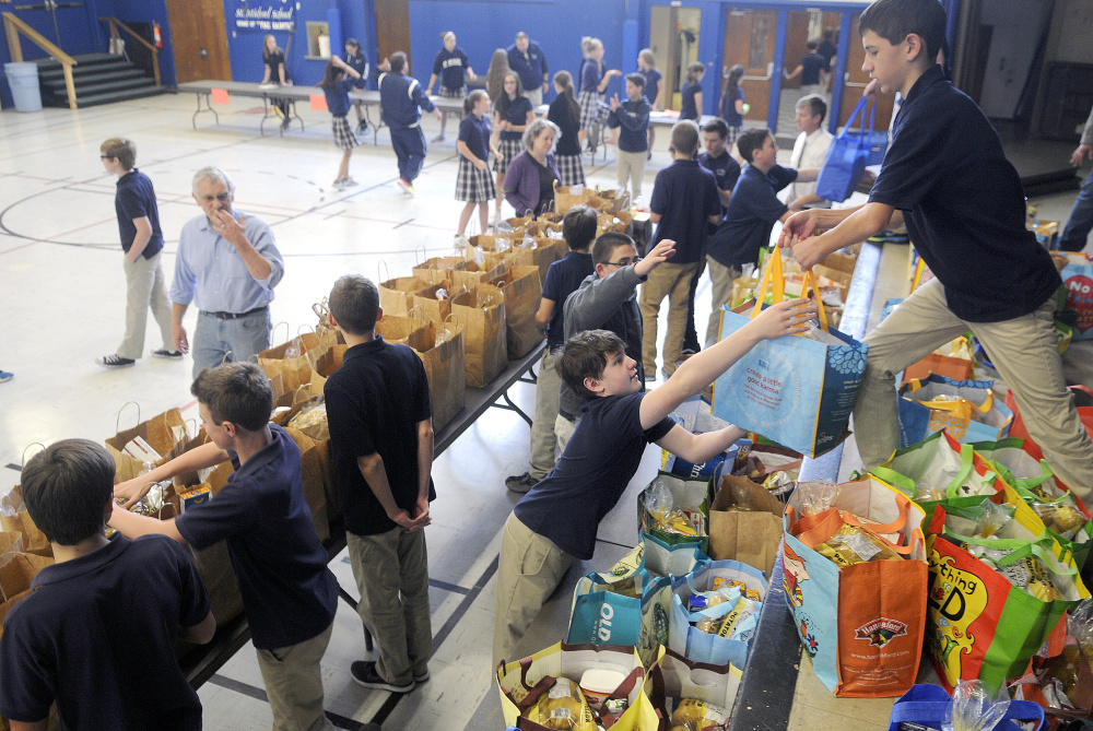 St. Michael eighth-graders Chris Bourdon, right, and Dom Brunelle prepare bags of groceries Monday for the Thanksgiving holiday at the private Catholic school in Augusta. Several people collected the donated meals assembled by the students.