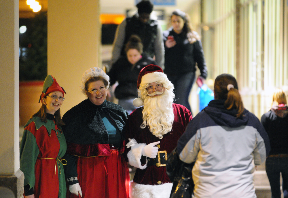 An elf accompanies Mrs. Claus and Santa Claus as they greet shoppers walking between stores Nov. 27, 2015 — which was Black Friday — at the Marketplace at Augusta in Augusta.