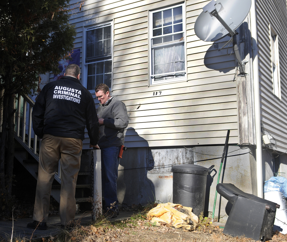 Augusta police Lt. Chris Massey, left, and Augusta Code Enforcement Officer Robert Overton conduct and inspection Wednesday at the apartment building at 117 Bridge St. in Augusta after police executed a search warrant there and arrested two people on drug trafficking charges.