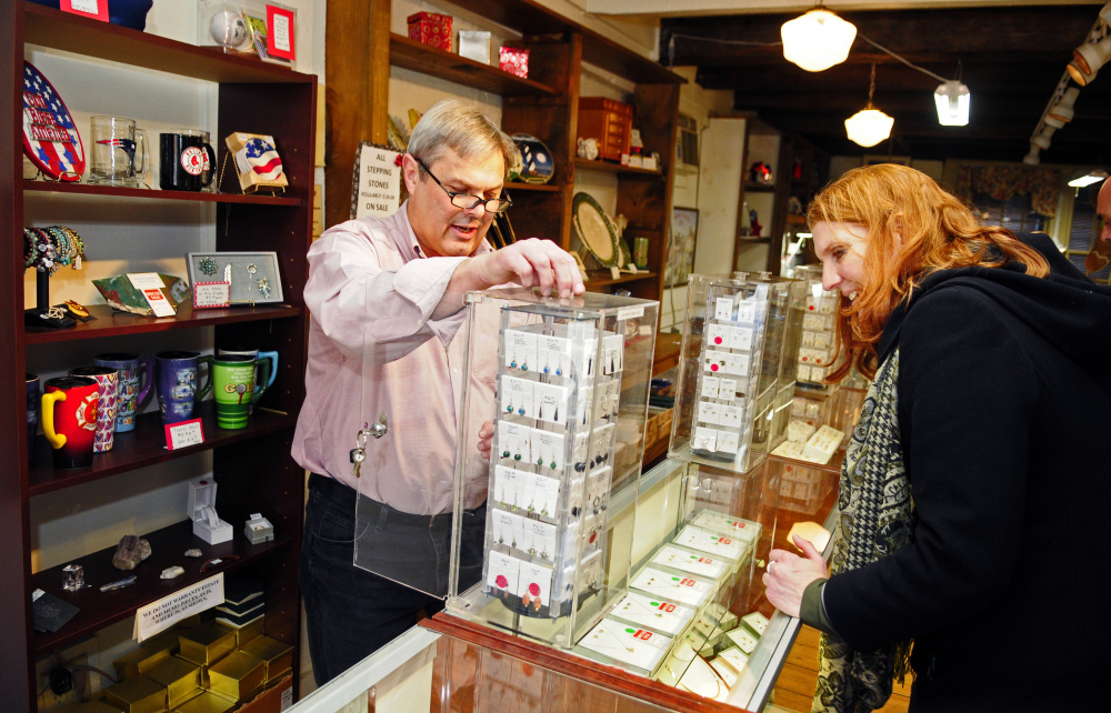 Jack Turner, left, takes earrings out of the case for Diane Sturgeon, Maine deputy district director of the Small Business Administration, during a promotional tour for Small Business Saturday on Wednesday at Jack B. Turner Jewelers in Hallowell.