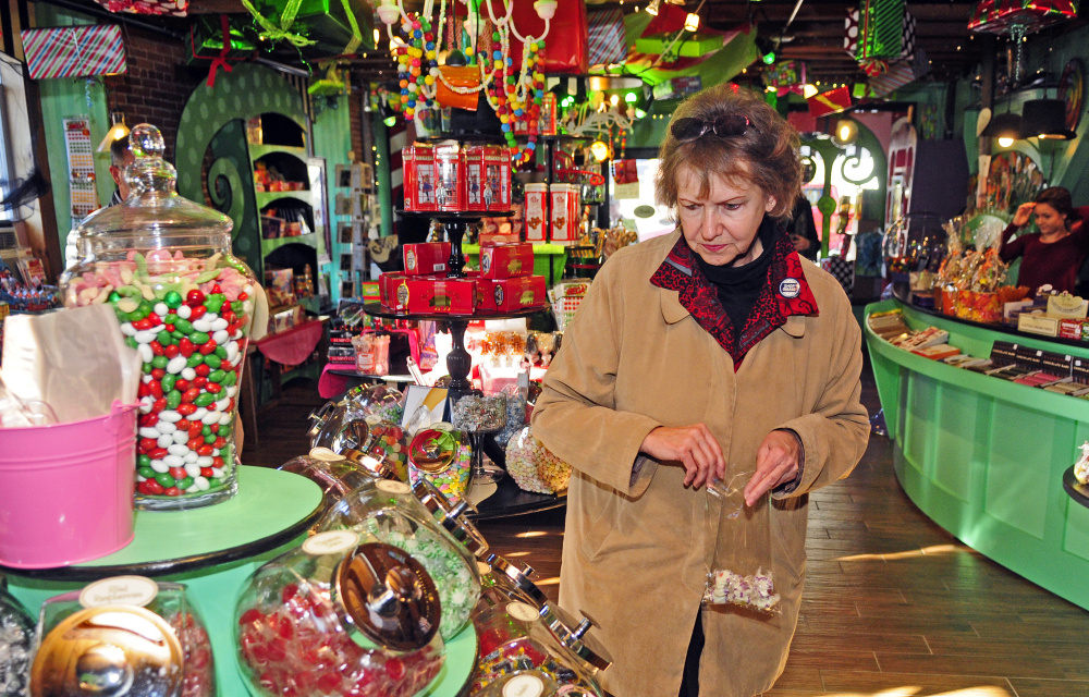 Marilyn Geroux, Maine district director of the Small Business Administration, buys candy during a promotional tour for Small Business Saturday on Wednesday at Scrummy Afters in Hallowell.