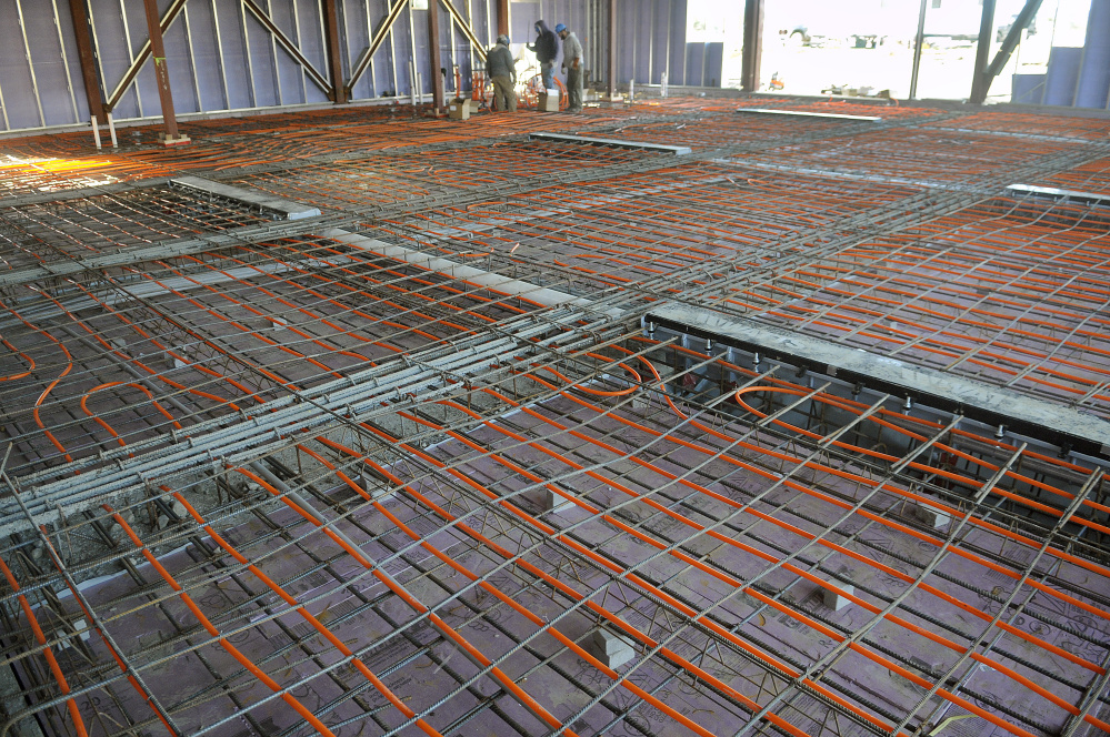 Workers install radiant heating beneath the bays last week at the new fire station in Augusta.