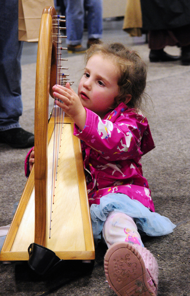 Dalais Belyeu, 3, of Albion, tries out a harp made and being offered for sale by Mellori Worthen during a craft show Saturday at the Augusta Civic Center.