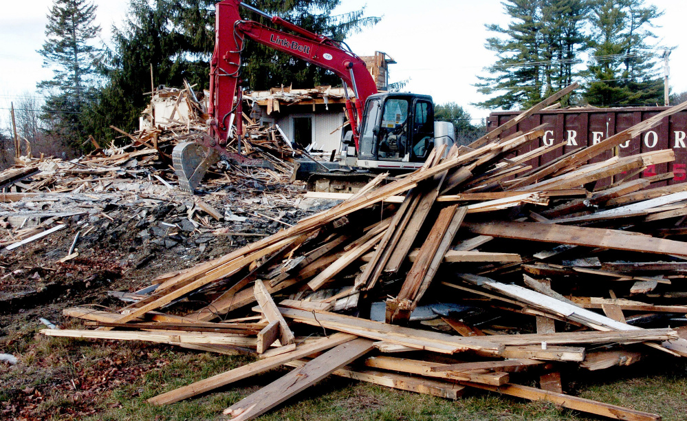 A farmhouse owned by the Trinity Evangelical Free Church in Skowhegan is torn down on Thursday. The two-story home at 84 Front St. in Skowhegan was demolished with plans to build a new 48-bed family shelter from the ground up.