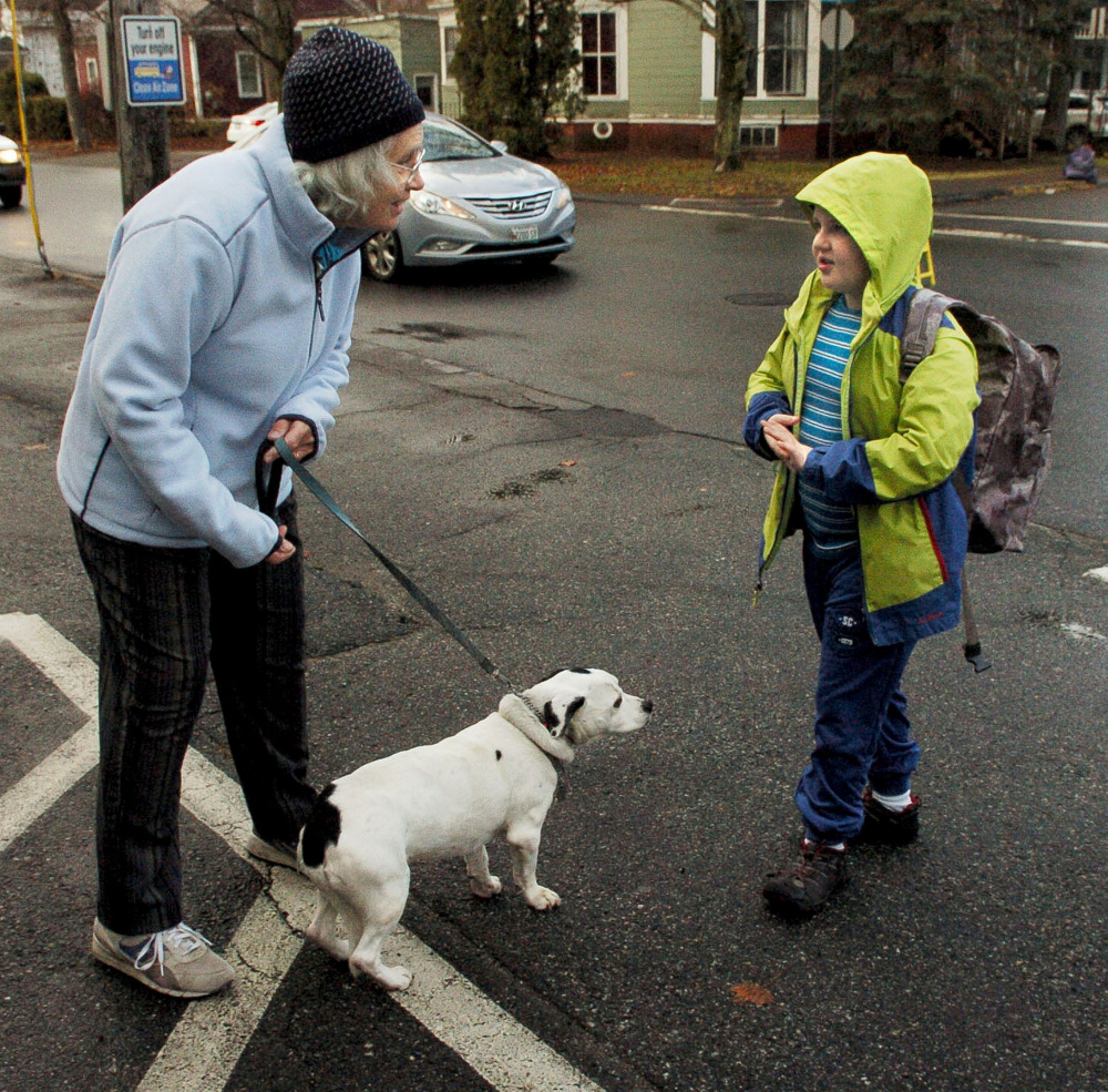 Cindy Longstaff and her dog, Wilbur, greet Albert S. Hall School student Nat Minot as he arrives for school in Waterville on Monday. Longstaff and Wilbur have met kids as they arrive on buses for four years, and 10-year-old Nat even wrote a poem about the friendly dog.