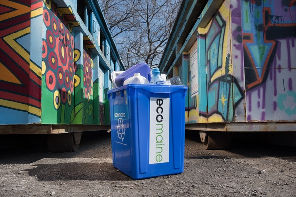 A single-sort recycling bin is seen in front of a painted recycling drop-off location for ecomaine.