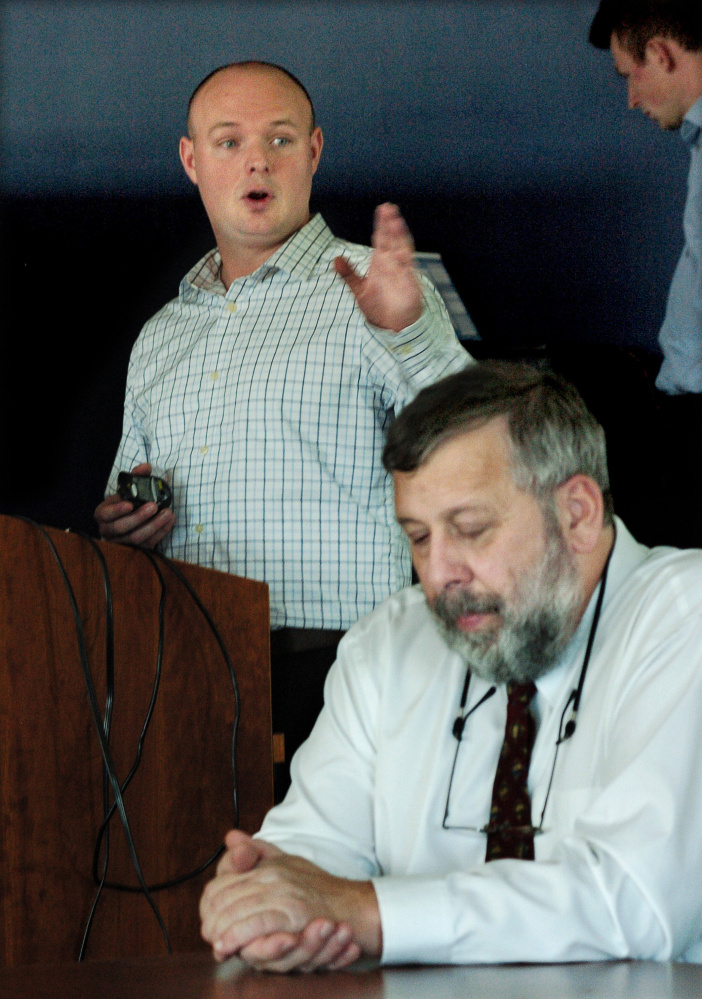 Cameron Wellman of the Maine Emergency Management Association gestures as he addresses municipal, hospital and law enforcement officials during a cybersecurity talk at Thomas College on Monday. Thomas College professor Frank Appunn, in foreground, also spoke.