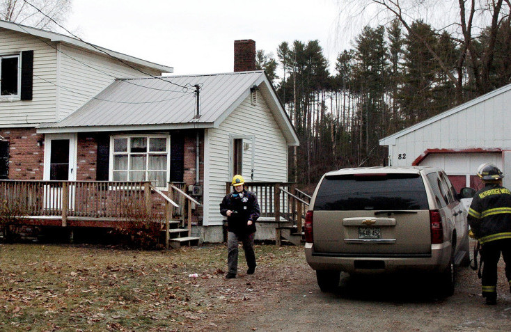 Office of the Maine State Fire Marshal investigator Mary MacMaster, left, and Norridgewock firefighters prepare to gather evidence Tuesday at a home at 82 Mechanic St. in Norridgewock that was damaged by fire the previous night.