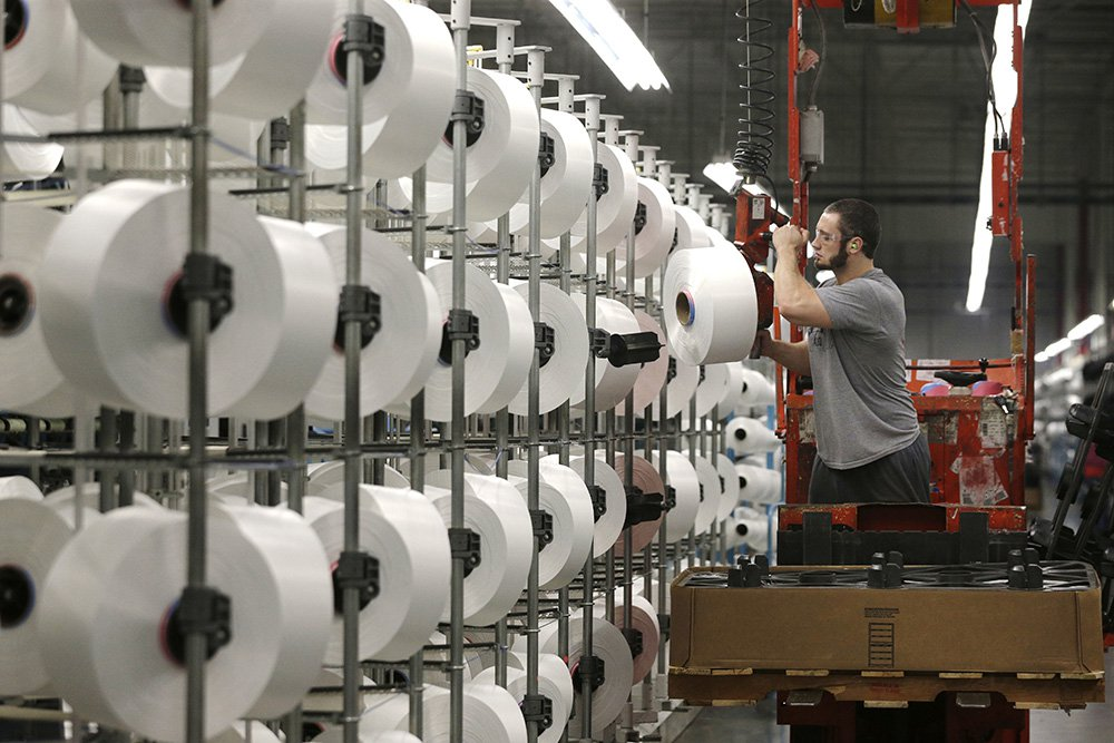 A worker loads spools of thread at the Repreve Bottle Processing Center, part of the Unifi textile company, in Yadkinville, N.C. Over the past six years, Unifi has added about 200 jobs, bringing the total to over 1,100.