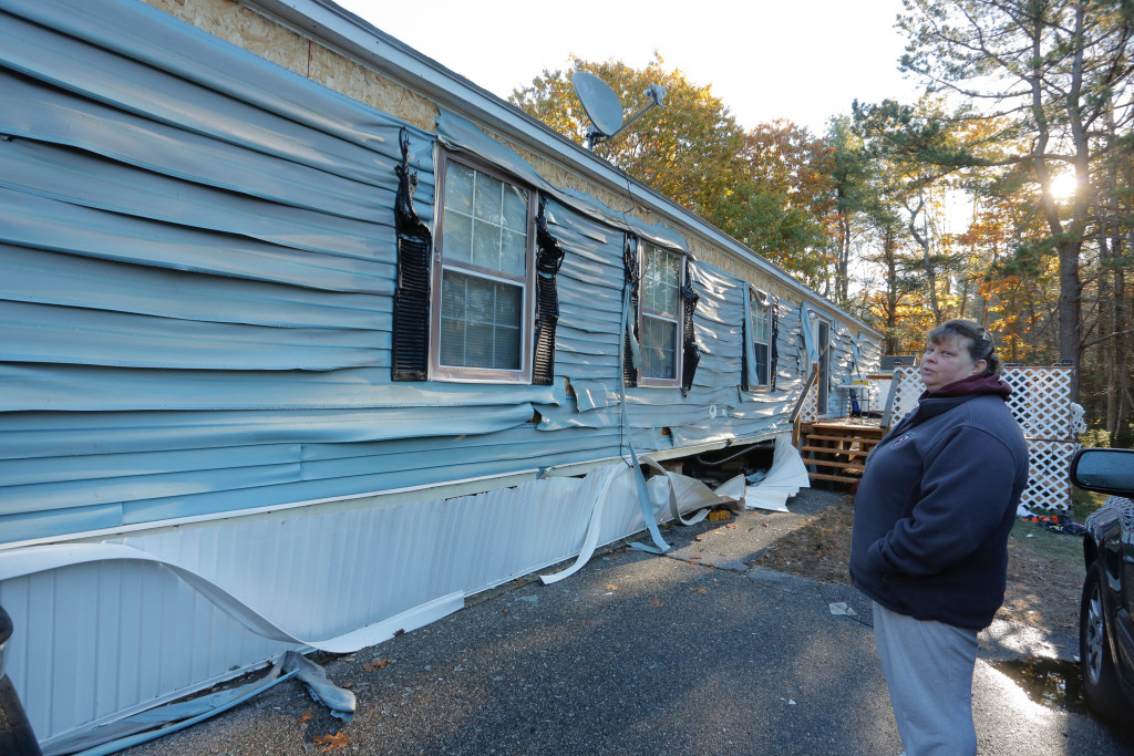 Kim Leclair looks at the melted vinyl siding on her trailer home on Pheasant Road in Saco on Tuesday morning. She and her husband, Bob, live next to the trailer home that exploded at 1:30 a.m. The heat from the fire melted the siding, but firefighters prevented the fire from spreading.