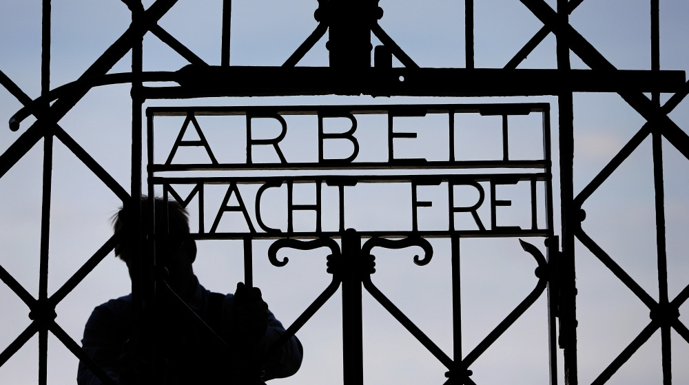 """A  blacksmith prepares a replica of the Dachau camp gate last year with the German slogan for """"Work sets you free."""""""