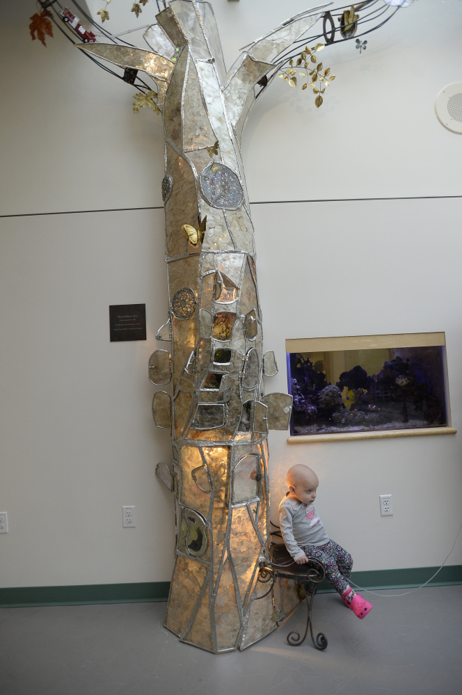 "Patient Madison Arndt sits in a small chair that is part of the stained-glass tree installed in the children's hospital atrium. ""She likes exploring it, looking in every door and seeing what she can find,"" said her father, Mitchell Arndt. ""It's pretty amazing. Lots of colors."""