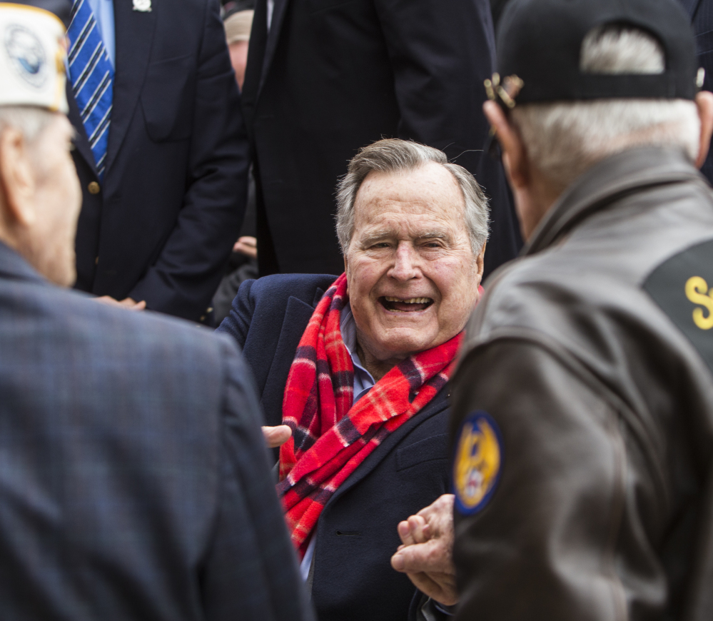 Former President George H.W. Bush greets World War II veterans at the conclusion of a Pearl Harbor remembrance ceremony at the George Bush Presidential Library on Wednesday in College Station, Texas.