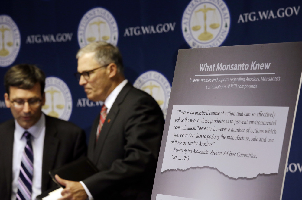 Washington Attorney General Bob Ferguson, left, and Gov. Jay Inslee announce a lawsuit against agrochemical giant Monsanto over pollution from polychlorinated biphenyls, or PCBs, in Seattle on Thursday.