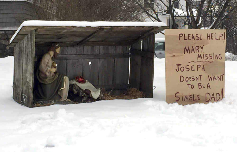 A handwritten, cardboard sign next to a nativity scene in Manchester, N.H., displays a message Monday for whomever stole the statue of Mary last week.