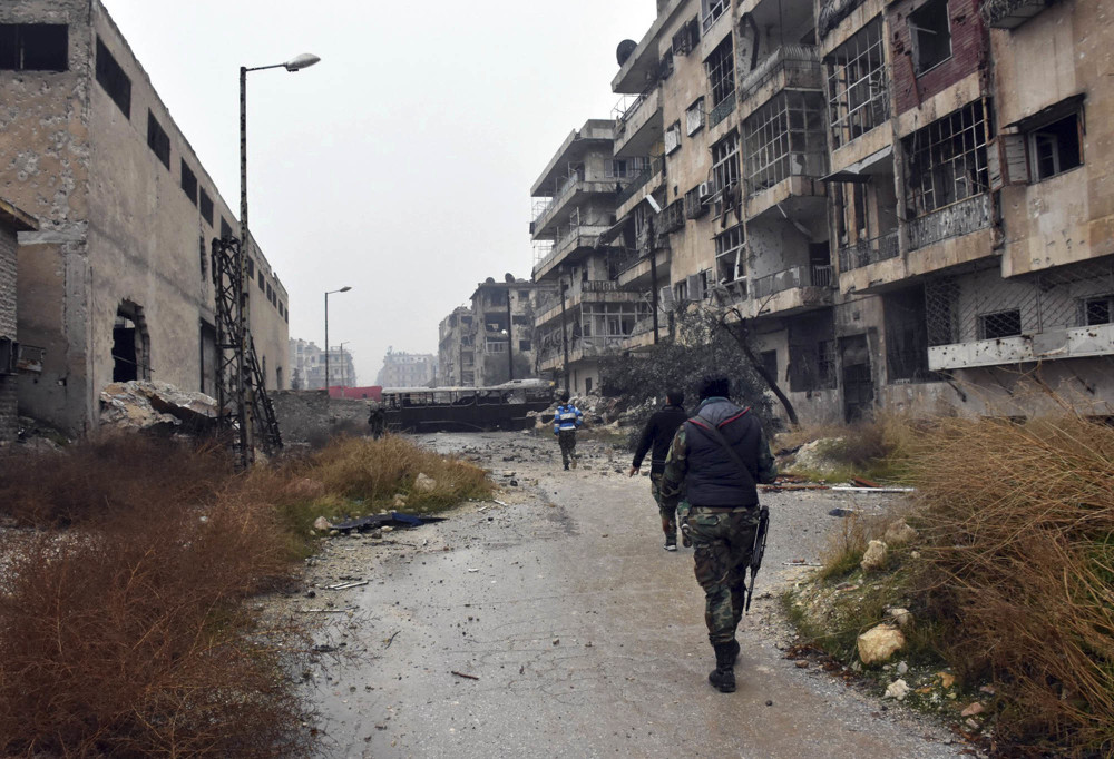 Syrian troops and pro-government gunmen march through the streets of east Aleppo, Syria, on Tuesday.