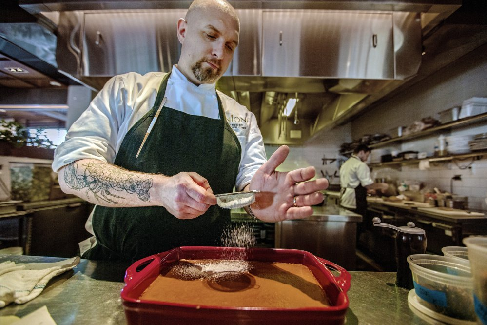 Josh Berry dusts Indian pudding with powdered sugar at Union restaurant in the Press Hotel.