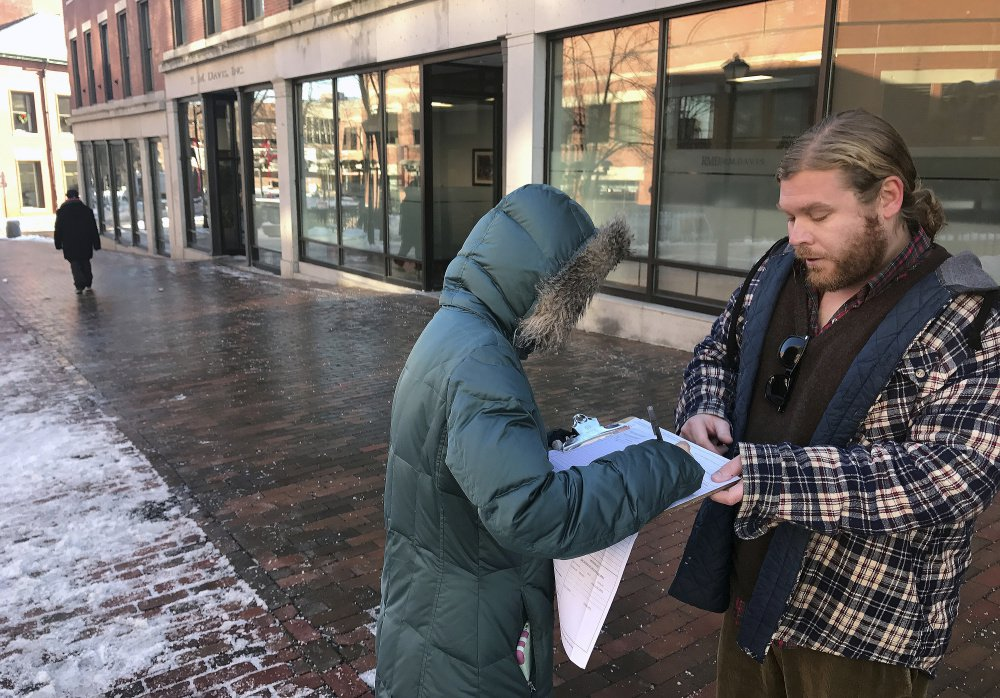 Tina Kartika, 24, of Portland signs a petition Tuesday to put Medicare expansion on the Maine ballot. George Frangoulis of Portland, working for the Maine People's Alliance, was gathering signatures in Monument Square.