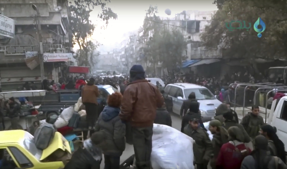 This image taken from video shows civilians gathering for evacuation from eastern Aleppo, Syria, on Thursday.